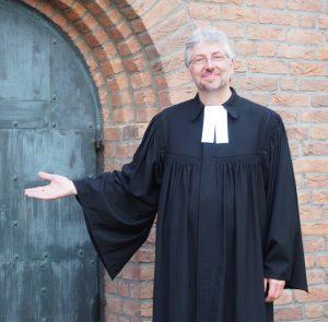 Mann mit grauen Haaren und grauem Bart im Talar vor einem Kirchenportal